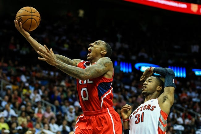 Nov 1, 2013; Atlanta, GA, USA; Atlanta Hawks point guard Jeff Teague (0) attempts a shot after being fouled by Toronto Raptors shooting guard Terrence Ross (31) in the second half at Philips Arena. The Hawks won 102-95. Mandatory Credit: Daniel Shirey-USA TODAY Sports