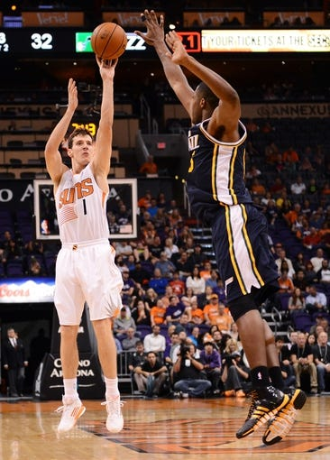 Nov 1, 2013; Phoenix, AZ, USA; Phoenix Suns guard Goran Dragic (1) puts up a shot against the Utah Jazz forward Derrick Favors (15) in the first half at US Airways Center. Mandatory Credit: Jennifer Stewart-USA TODAY Sports