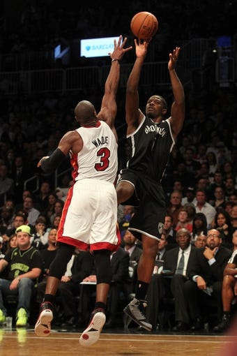 Nov 1, 2013; Brooklyn, NY, USA; Brooklyn Nets shooting guard Joe Johnson (7) shoots over Miami Heat shooting guard Dwyane Wade (3) during the third quarter of a game at Barclays Center. Mandatory Credit: Brad Penner-USA TODAY Sports