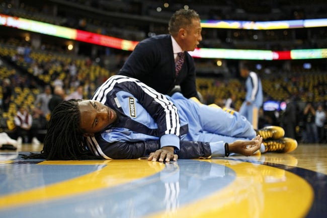 Nov 1, 2013; Denver, CO, USA; Strength and conditioning coach Steve Hess (behind) stretches out Denver Nuggets small forward Kenneth Faried (35) before the start of the game against the Portland Trail Blazers at the Pepsi Center. The Trail Blazers won 113-98. Mandatory Credit: Isaiah J. Downing-USA TODAY Sports