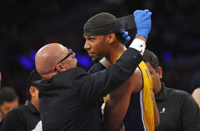 November 1, 2013; Los Angeles, CA, USA; Los Angeles Lakers shooting guard Xavier Henry (7) has a bandage applied by trainer Gary Vitti during a stoppage in play in the first half at Staples Center. Mandatory Credit: Gary A. Vasquez-USA TODAY Sports