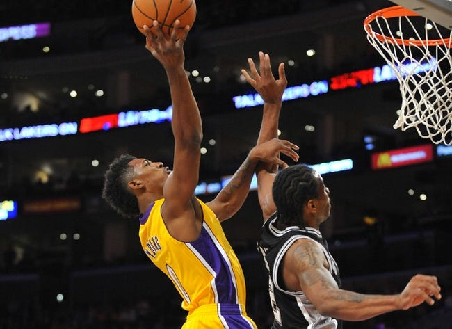 November 1, 2013; Los Angeles, CA, USA; Los Angeles Lakers shooting guard Nick Young (0) goes in for a basket against the defense of San Antonio Spurs small forward Kawhi Leonard (2) during the first half at Staples Center. Mandatory Credit: Gary A. Vasquez-USA TODAY Sports