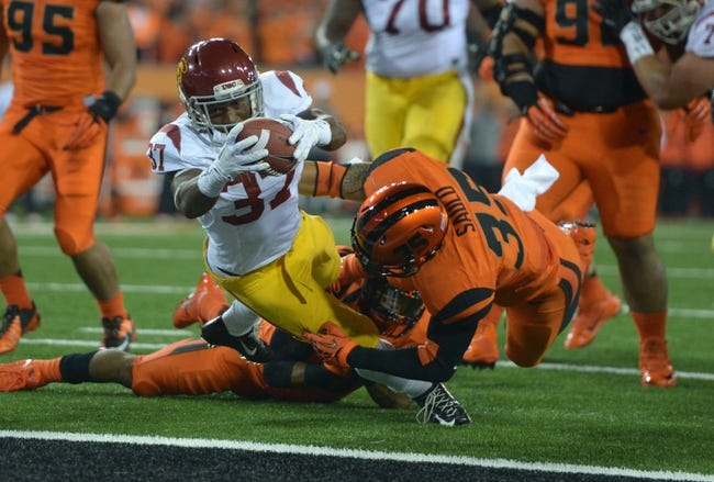 Nov 1, 2013; Corvallis, OR, USA; Southern California Trojans tailback Javorious Allen (37) is defended by Oregon State Beavers linebacker Caleb Saulo (35) on a 9-yard touchdown run in the first quarter at Reser Stadium. Mandatory Credit: Kirby Lee-USA TODAY Sports