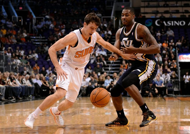 Nov 1, 2013; Phoenix, AZ, USA; Phoenix Suns guard Goran Dragic (1) watches the ball while being defended byUtah Jazz forward Derrick Favors (15) in the first half at US Airways Center. The Suns defeated the Jazz 87-84.  Mandatory Credit: Jennifer Stewart-USA TODAY Sports