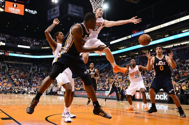 Nov 1, 2013; Phoenix, AZ, USA; Utah Jazz guard Alec Burks (10) makes a pass to center Enes Kanter (0) as Phoenix Suns forward Miles Plumlee (22) defends in the second half at US Airways Center.  The Suns defeated the Jazz 87-84. Mandatory Credit: Jennifer Stewart-USA TODAY Sports