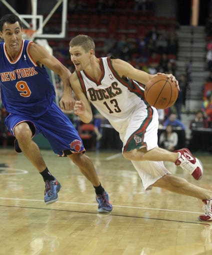 Oct 23, 2013; Green Bay, WI, USA; Milwaukee Bucks point guard Luke Ridnour (13) drives the ball down the floor as New York Knicks guard Pablo Prigioni (9) defends at the Resch Center in Green Bay. The Bucks defeated the Knicks 105-95. Mandatory Credit: Mary Langenfeld-USA TODAY Sports