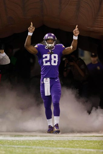 Oct 27, 2013; Minneapolis, MN, USA; Minnesota Vikings running back Adrian Peterson (28) enters the field as he is introduced to play against the Green Bay Packers at Mall of America Field at H.H.H. Metrodome. The Packers win 44-31. Mandatory Credit: Bruce Kluckhohn-USA TODAY Sports