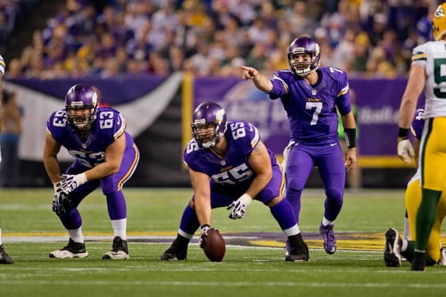 Oct 27, 2013; Minneapolis, MN, USA; Minnesota Vikings quarterback Christian Ponder (7) calls out the Green Bay Packers defense to offensive lineman Brandon Fusco (63) and center John Sullivan (65) in the second quarter at Mall of America Field at H.H.H. Metrodome. The Packers win 44-31. Mandatory Credit: Bruce Kluckhohn-USA TODAY Sports