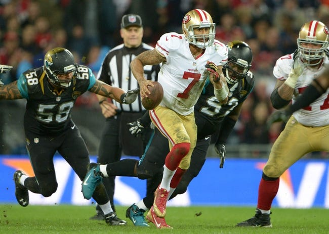 Oct 27, 2013; London, United Kingdom; San Francisco 49ers quarterback Colin Kapernick (7) is pursued by Jacksonville Jaguars defensive end Jason Babiin (58) and defensive tackle Brandon Deaderick (92) in the NFL International Series game at Wembley Stadium. The 49ers defeated the Jaguars 42-10. Mandatory Credit: Kirby Lee-USA TODAY Sports