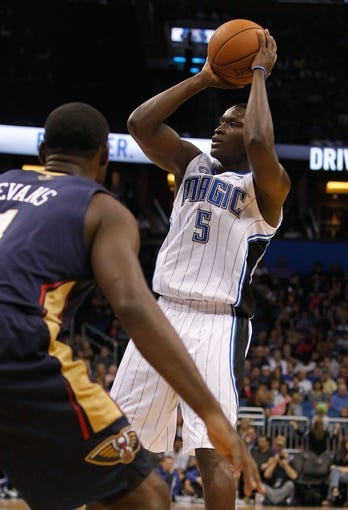 Oct 25, 2013; Orlando, FL, USA;Orlando Magic shooting guard Victor Oladipo (5) shoots as New Orleans Pelicans point guard Tyreke Evans (1) defends  during the first quarter at Amway Center. Mandatory Credit: Kim Klement-USA TODAY Sports