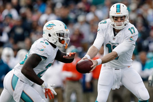 Oct 27, 2013; Foxborough, MA, USA; Miami Dolphins quarterback Ryan Tannehill (17) hands off to Miami Dolphins running back Lamar Miller (26) against the New England Patriots during the first quarter at Gillette Stadium. Mandatory Credit: Winslow Townson-USA TODAY Sports
