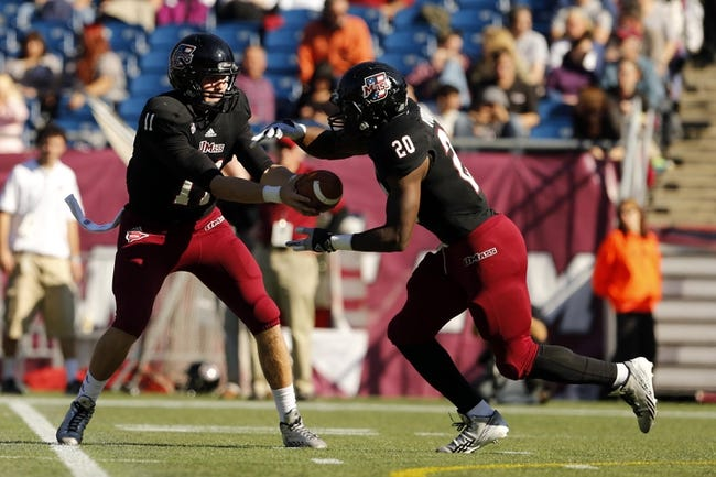 Nov 2, 2013; Foxborough, MA, USA; Massachusetts Minutemen quarterback Mike Wegzyn (11) hands off the ball to running back Lorenzo Woodley (20) against the Northern Illinois Huskies during the second quarter at Gillette Stadium. Mandatory Credit: David Butler II-USA TODAY Sports