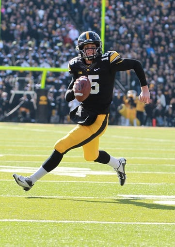 Nov 2, 2013; Iowa City, IA, USA;  Iowa Hawkeyes quarterback Jake Rudock (15) runs for a first down against the Wisconsin Badgers in the first half at Kinnick Stadium. Mandatory Credit: Reese Strickland-USA TODAY Sports