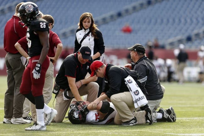 Nov 2, 2013; Foxborough, MA, USA; Northern Illinois Huskies offensive linesman Tyler Loos (75) is tended to by head coach Rod Carey and others after being injured as they take on the Massachusetts Minutemen during the second half at Gillette Stadium. Northern Illinois defeated Massachusetts 63-19. Mandatory Credit: David Butler II-USA TODAY Sports
