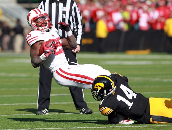 Nov 2, 2013; Iowa City, IA, USA;  Wisconsin Badgers running back Melvin Gordon (25) is tackled by Desmond King (14) of the Iowa Hawkeyes at Kinnick Stadium.  Wisconsin beat Iowa 28-9.  Mandatory Credit: Reese Strickland-USA TODAY Sports