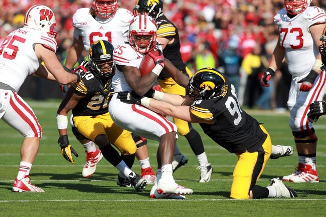 Nov 2, 2013; Iowa City, IA, USA;  Wisconsin Badgers running back Melvin Gordon (25) is tackled by Mike Hardy (98) and Christian Kirksey (20) of the Iowa Hawkeyes at Kinnick Stadium.  Wisconsin beat Iowa 28-9.  Mandatory Credit: Reese Strickland-USA TODAY Sports