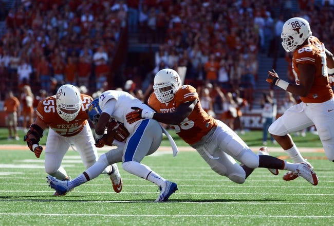 Nov 2, 2013; Austin, TX, USA; Texas Longhorns linebackers Steve Edmund (33) and Dalton Santos (55) tackle Kansas Jayhawks quarterback Montell Cozart (2) during the second quarter at Darrell K Royal-Texas Memorial Stadium. Mandatory Credit: Brendan Maloney-USA TODAY Sports