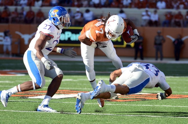 Nov 2, 2013; Austin, TX, USA; Texas Longhorns wide receiver Marcus Johnson (7) is tackled by Kansas Jayhawks safety Cassius Sendish (33) and nickleback Victor Simmons (27) during the third quarter at Darrell K Royal-Texas Memorial Stadium. Texas beat Kansas 35-13. Mandatory Credit: Brendan Maloney-USA TODAY Sports
