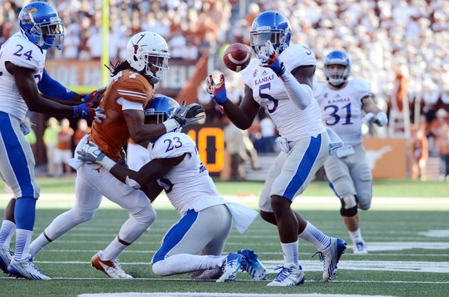 Nov 2, 2013; Austin, TX, USA; Kansas Jayhawks safety Isaiah Johnson (5) intercepts a pass intended for Texas Longhorns wide receiver Marcus Johnson (7) during the fourth quarter at Darrell K Royal-Texas Memorial Stadium. Texas beat Kansas 35-13. Mandatory Credit: Brendan Maloney-USA TODAY Sports