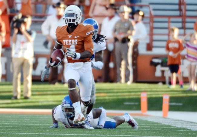 Nov 2, 2013; Austin, TX, USA; Texas Longhorns kick returner Daje Johnson (4) runs the ball against the Kansas Jayhawks during the fourth quarter at Darrell K Royal-Texas Memorial Stadium. Texas beat Kansas 35-13. Mandatory Credit: Brendan Maloney-USA TODAY Sports