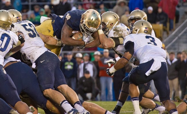 Nov 2, 2013; South Bend, IN, USA; Notre Dame Fighting Irish running back Tarean Folston (25) dives into the end zone for a touchdown as Navy Midshipmen linebacker Cody Peterson (53) defends in the fourth quarter at Notre Dame Stadium. Notre Dame won 38-34. Mandatory Credit: Matt Cashore-USA TODAY Sports