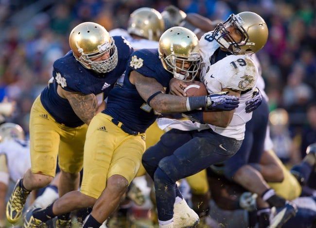 Nov 2, 2013; South Bend, IN, USA; Navy Midshipmen quarterback Keenan Reynolds (19) is hit by Notre Dame Fighting Irish safety Eilar Hardy (16) in the fourth quarter at Notre Dame Stadium. Notre Dame won 38-24. Mandatory Credit: Matt Cashore-USA TODAY Sports