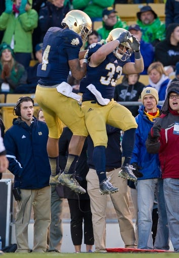 Nov 2, 2013; South Bend, IN, USA; Notre Dame Fighting Irish running back Cam McDaniel (33) celebrates with running back George Atkinson III (4) after scoring a touchdown in the fourth quarter against the Navy Midshipmen at Notre Dame Stadium. Notre Dame won 38-34. Mandatory Credit: Matt Cashore-USA TODAY Sports