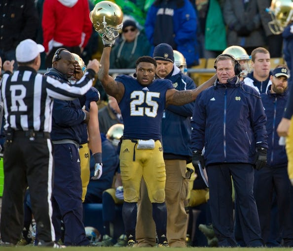 Nov 2, 2013; South Bend, IN, USA; Notre Dame Fighting Irish running back Tarean Folston (25) reacts as referee Ed Ardito announces the result of a reviewed play in the fourth quarter against the Navy Midshipmen at Notre Dame Stadium. Notre Dame won 38-34. Mandatory Credit: Matt Cashore-USA TODAY Sports