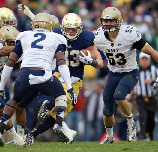 Nov 2, 2013; South Bend, IN, USA; Notre Dame Fighting Irish running back Cam McDaniel (33) carries the ball in the second quarter as Navy Midshipmen cornerback Parrish Gaines (2) and linebacker Cody Peterson (53) defend at Notre Dame Stadium. Notre Dame won 38-34. Mandatory Credit: Matt Cashore-USA TODAY Sports