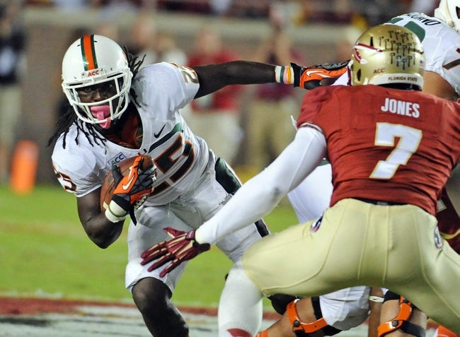Nov 2, 2013; Tallahassee, FL, USA; Miami Hurricanes running back Dallas Crawford (25) runs the ball past Florida State Seminoles linebacker Christian Jones (7) during the first half at Doak Campbell Stadium. Mandatory Credit: Melina Vastola-USA TODAY Sports
