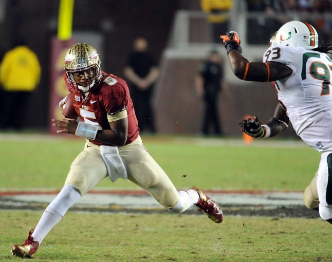 Nov 2, 2013; Tallahassee, FL, USA; Florida State Seminoles quarterback Jameis Winston (5) makes a move to avoid Miami Hurricanes defensive lineman Luther Robinson (93) during the second half at Doak Campbell Stadium. Mandatory Credit: Melina Vastola-USA TODAY Sports