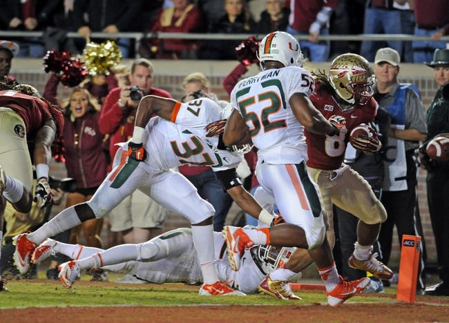 Nov 2, 2013; Tallahassee, FL, USA; Florida State Seminoles running back Devonta Freeman (8) scores a touchdown past Miami Hurricanes linebacker Denzel Perryman (52) and defensive back Alex Irastorza (37) during the second half at Doak Campbell Stadium. Mandatory Credit: Melina Vastola-USA TODAY Sports