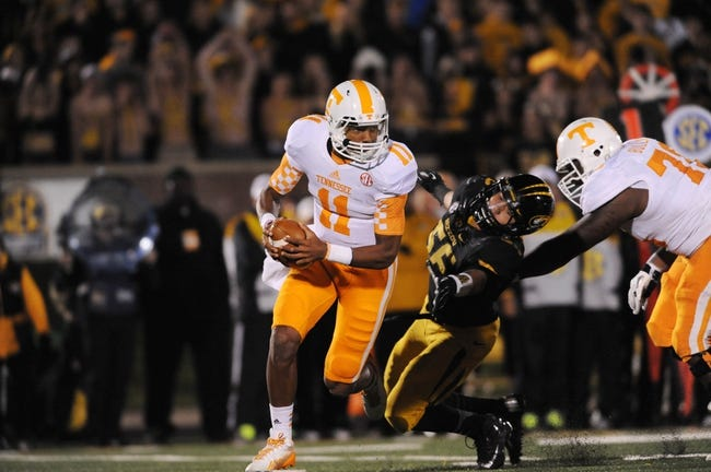 Nov 2, 2013; Columbia, MO, USA; Tennessee Volunteers quarterback Joshua Dobbs (11) scrambles behind the line as Missouri Tigers defensive lineman Shane Ray (56) attempts the sack during the second half of the game at Faurot Field. Missouri won 31-3. Mandatory Credit: Denny Medley-USA TODAY Sports