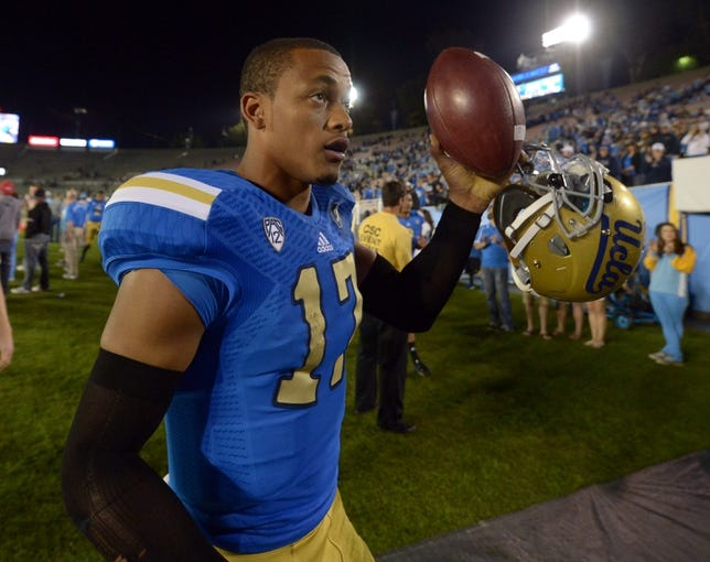 Nov 2, 2013; Pasadena, CA, USA; UCLA Bruins quarterback Brett Hundley (17) walks off the field with the game ball after the game against the Colorado Buffaloes at Rose Bowl. UCLA defeated Colorado 45-23. Mandatory Credit: Kirby Lee-USA TODAY Sports