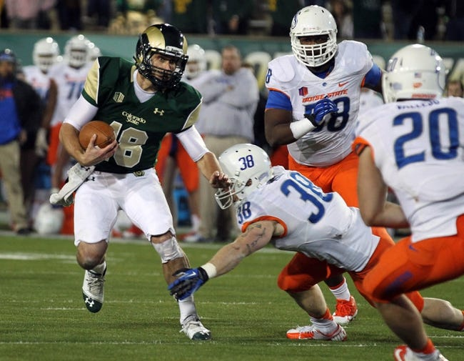 Nov 2, 2013; Fort Collins, CO, USA; Colorado State Rams quarterback Garrett Grayson (18) runs against Boise State Broncos linebackers Corey Bell (38) and Tanner Vallejo (20) during the fourth quarter at Hughes Stadium. Mandatory Credit: Troy Babbitt-USA TODAY Sports