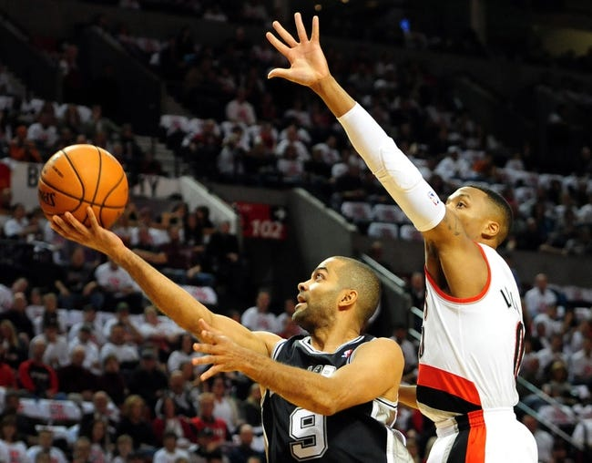 Nov 2, 2013; Portland, OR, USA; San Antonio Spurs point guard Tony Parker (9) drives to the basket on Portland Trail Blazers point guard Damian Lillard (0) during the first quarter of the game at the Moda Center. Mandatory Credit: Steve Dykes-USA TODAY Sports