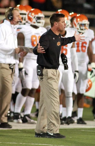 Nov 2, 2013; Lubbock, TX, USA; Oklahoma State Cowboys head coach Mike Gundy questions a call in the game against the Texas Tech Red Raiders at Jones AT&T Stadium. Mandatory Credit: Michael C. Johnson-USA TODAY Sports