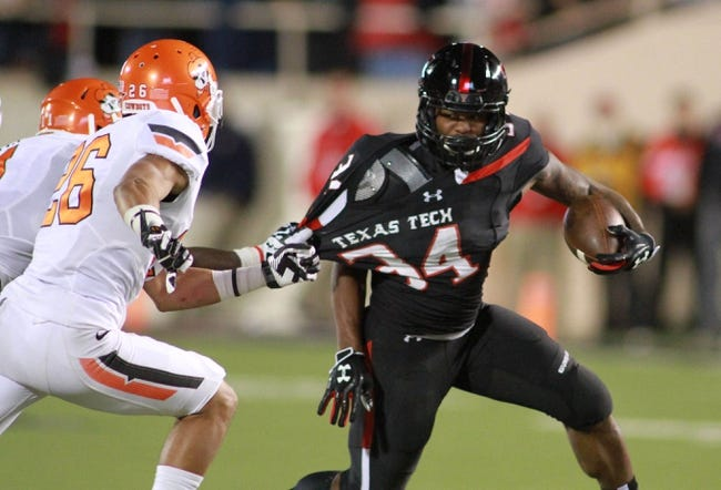 Nov 2, 2013; Lubbock, TX, USA; Texas Tech Red Raiders running back Kenny Williams (34) tries to escape the Oklahoma State Cowboys defense in the second half  at Jones AT&T Stadium. Mandatory Credit: Michael C. Johnson-USA TODAY Sports