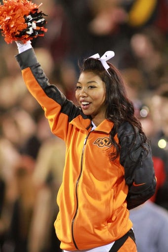 Nov 2, 2013; Lubbock, TX, USA; An Oklahoma State Cowboys cheerleader shows her support in the game against the Texas Tech Red Raiders at Jones AT&T Stadium. Mandatory Credit: Michael C. Johnson-USA TODAY Sports