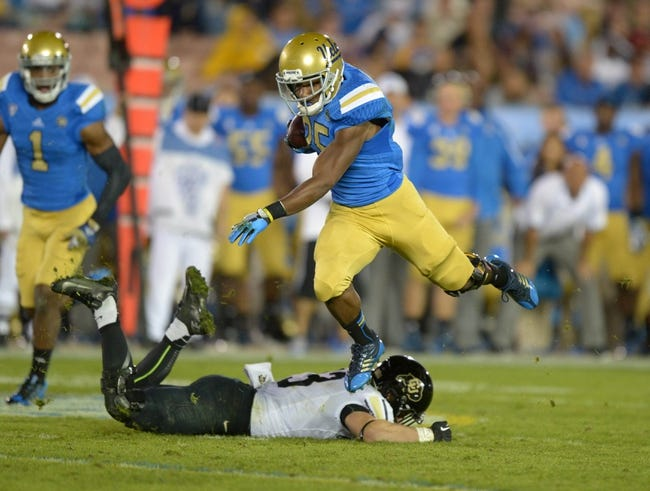 Nov 2, 2013; Pasadena, CA, USA; UCLA Bruins running back Damien Thigpen (25) leaps over Colorado Buffaloes safety Parker Orms (13) at Rose Bowl. UCLA defeated Colorado 45-23. Mandatory Credit: Kirby Lee-USA TODAY Sports