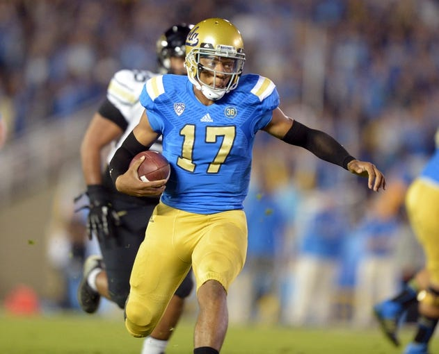 Nov 2, 2013; Pasadena, CA, USA; UCLA Bruins quarterback Brett Hundley (17) carries the ball against the Colorado Buffaloes at Rose Bowl. UCLA defeated Colorado 45-23. Mandatory Credit: Kirby Lee-USA TODAY Sports