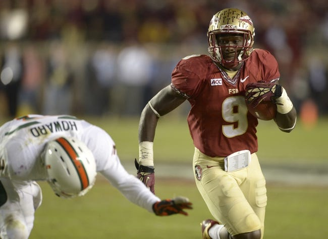 Nov 2, 2013; Tallahassee, FL, USA; Florida State Seminoles running back Karlos Williams (9) carries past Miami Hurricanes defensive back Tracy Howard (3) during the fourth quarter at Doak Campbell Stadium. The Florida State Seminoles defeated the Miami Hurricanes 41-14. Mandatory Credit: John David Mercer-USA TODAY Sports