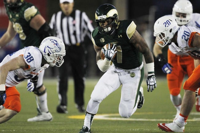 Nov 2, 2013; Fort Collins, CO, USA; Colorado State Rams running back Donnell Alexander (7) runs against Boise State Broncos linebackers Corey Bell (38) and Tanner Vallejo (20) during the first quarter at Hughes Stadium. The Broncos defeated the Rams 42-30. Mandatory Credit: Troy Babbitt-USA TODAY Sports