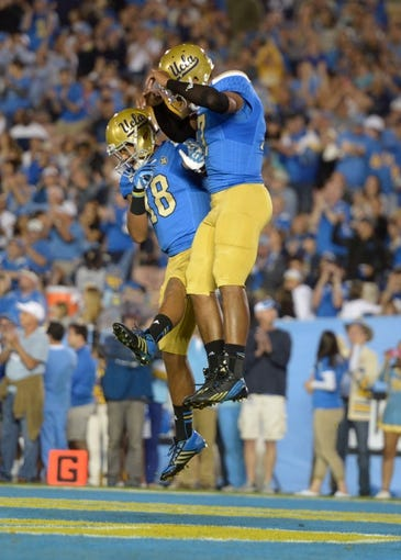 Nov 2, 2013; Pasadena, CA, USA; UCLA Bruins quarterback Brett Hundley (17) celebrates with receiver Thomas Duarte (18) after scoring on a 1-yard touchdown run in the third quarter against the Colorado Buffaloes at Rose Bowl. UCLA defeated Colorado 45-23. Mandatory Credit: Kirby Lee-USA TODAY Sports