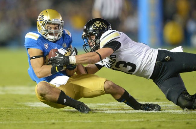 Nov 2, 2013; Pasadena, CA, USA; UCLA Bruins receiver Grayson Mazzone (83) is defended by Colorado Buffaloes safety Parker Orms (13) on a 20-yard reception at Rose Bowl. UCLA defeated Colorado 45-23. Mandatory Credit: Kirby Lee-USA TODAY Sports