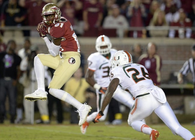 Nov 2, 2013; Tallahassee, FL, USA; Florida State Seminoles wide receiver Kenny Shaw (81) hauls in a pass over Miami Hurricanes defensive back Rayshawn Jenkins (26) during the third quarter at Doak Campbell Stadium. The Florida State Seminoles defeated the Miami Hurricanes 41-14. Mandatory Credit: John David Mercer-USA TODAY Sports