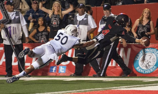 Nov 2, 2013; Fresno, CA, USA; Fresno State Bulldogs quarterback Derek Carr (4) avoids Nevada Wolf Pack linebacker Jonathan McNeal (50) while diving for the end zone during the second quarter at Bulldog Stadium. Mandatory Credit: Ed Szczepanski-USA TODAY Sports