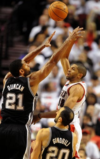 Nov 2, 2013; Portland, OR, USA; Portland Trail Blazers small forward Nicolas Batum (88) shoots the ball over San Antonio Spurs power forward Tim Duncan (21) and shooting guard Manu Ginobili (20) during the fourth quarter of the game at  the Moda Center. The Blazers won the game 115-105. Mandatory Credit: Steve Dykes-USA TODAY Sports