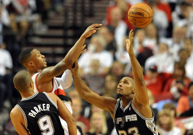 Nov 2, 2013; Portland, OR, USA; Portland Trail Blazers point guard Damian Lillard (0) passes the ball away from San Antonio Spurs point guard Tony Parker (9) and power forward Boris Diaw (33) during the fourth quarter of the game at the Moda Center. The Blazers won the game 115-105. Mandatory Credit: Steve Dykes-USA TODAY Sports