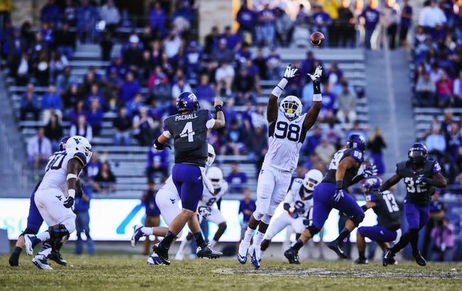 Nov 2, 2013; Fort Worth, TX, USA; TCU Horned Frogs quarterback Casey Pachall (4) throws a pass over West Virginia Mountaineers defensive lineman Will Clarke (98) during the game at Amon G. Carter Stadium. West Virginia won 30-27. Mandatory Credit: Kevin Jairaj-USA TODAY Sports
